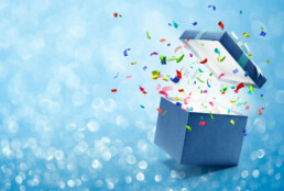 Confetti popping out from blue gift box
