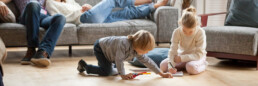 little kids playing on floor of living room with parents resting on couch